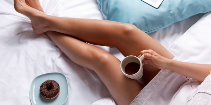 Woman's legs on bed with donut and coffee