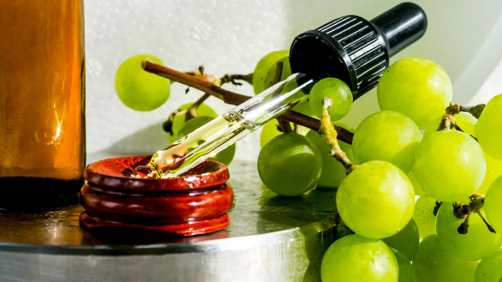 Grapes next to dropper with grape oil
