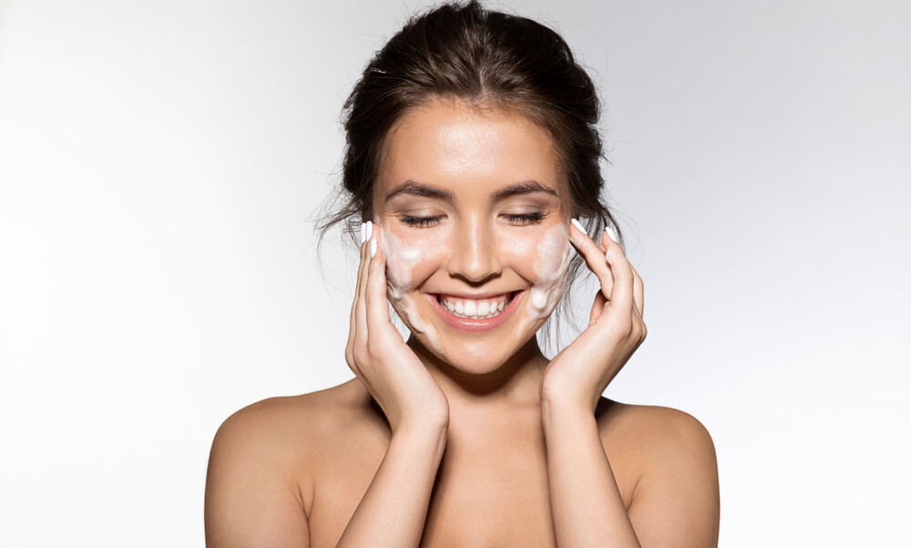 Woman applying cleanser to face
