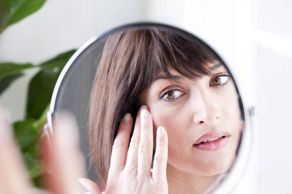 Woman looking at skin in mirror wondering how to treat wrinkle under eye