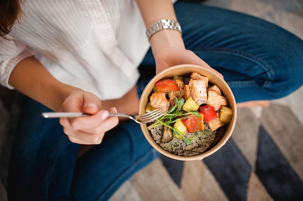 Woman eating bowl of healthy food